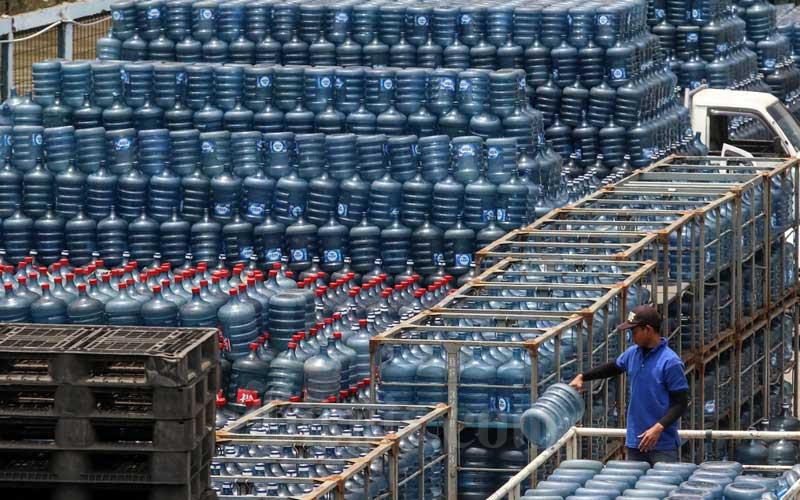 Pekerja melakukan bongkar muat air minum dalam kemasan di Jakarta, Senin (22/2/2021). Indonesia Water Institute (IWI) menyatakan ada peningkatan biaya air bersih selama pandemi Covid-19, peningkatan konsumsi produk air minum dalam kemasan (AMDK) diduga menjadi pendorong utama peningkatan biaya tersebut. Berdasarkan data IWI ada sekitar 65 persen masyarakat yang melakukan transisi dari penggunaan air tanah sebagai air minum menjadi produk AMDK, transisi terbesar terlihat pada kelompok masyarakat dengan biaya air Rp300.000-Rp1 juta per bulan. Bisnis/Eusebio Chrysnamurti
