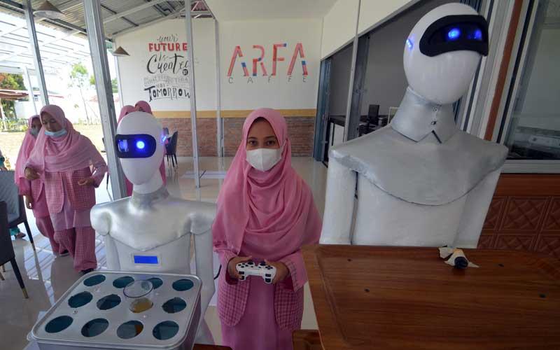 Sebuah robot mengantarkan minuman di Kafe Arfa, Perguruan Diniyah Putri Padangpanjang, Sumatera Barat, Senin (22/2/2021). Robot pelayan kafe yang dinamai Sabai dan Midun itu diciptakan santri Perguruan Diniyah Putri Padangpanjang menggunakan sistem remote kontrol dan pengikut garis magnet (line follower), yang dapat mengantarkan pesanan makanan ke meja pelanggan. ANTARA FOTO/Iggoy el Fitra