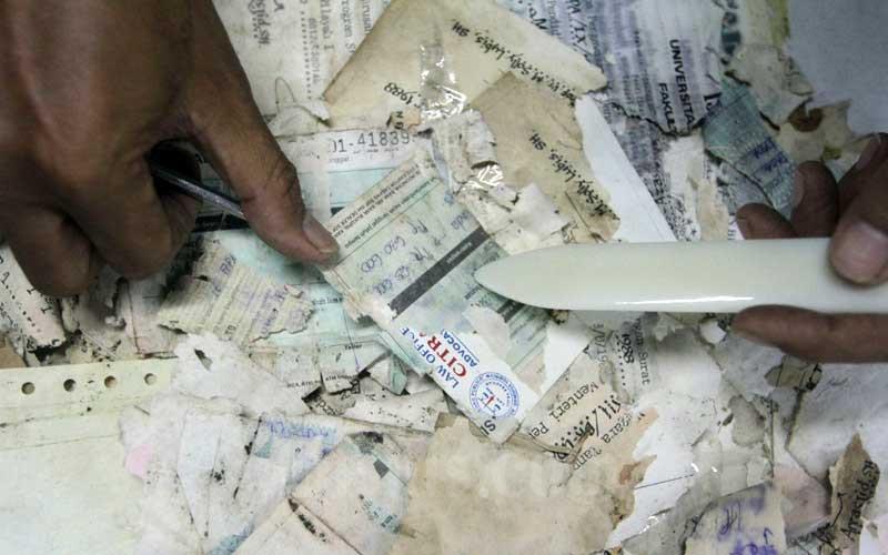 Petugas restorasi arsip melakukan perbaikan dokumen yang rusak akibat banjir di kantor Arsip Nasional Republik Indonesia (ANRI) di Jakarta, Senin (22/2/2021). ANRI membuka layanan pemulihan dokumen yang rusak bagi korban banjir seperti ijazah, akte kelahiran, sertifikat tanah, KK, KTP hingga STNK. Adapun perbaikan dokumen tersebut membutuhkan waktu 1 hingga 4 minggu. Bisnis/Himawan L Nugraha