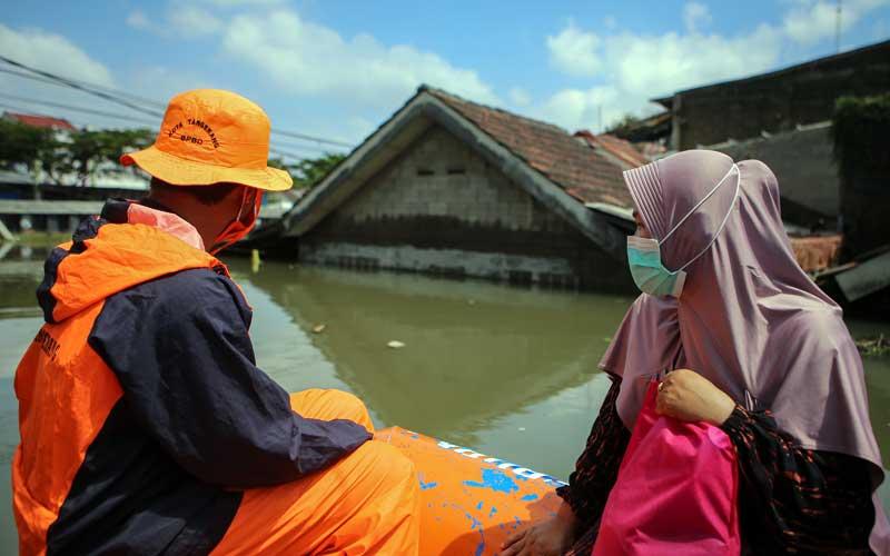 Petugas mengevakuasi warga menggunakan perahu karet saat banjir di Total Persada, Periuk, Kota Tangerang, Banten, Senin (22/2/2021). Memasuki hari ketiga, kawasan tersebut masih terendam banjir hingga setinggi 2,5 meter akibat luapan Kali Leduk. ANTARA FOTO/Fauzan