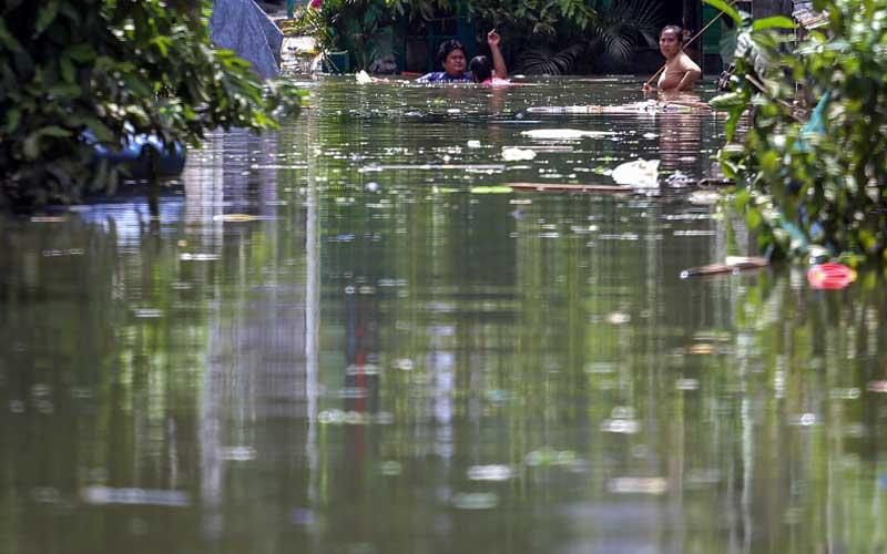 Warga berjalan di tengah banjir di Total Persada, Periuk, Kota Tangerang, Banten, Senin (22/2/2021). Memasuki hari ketiga, kawasan tersebut masih terendam banjir hingga setinggi 2,5 meter akibat luapan Kali Leduk. ANTARA FOTO/Fauzan