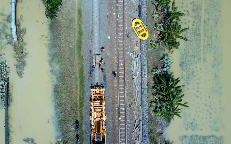 Foto udara proses perbaikan rel Kereta API di Kedungwaringin, Kabupaten Bekasi, Jawa Barat, Senin (22/2/2021). PT KAI membatalkan sementara perjalanan Kereta API (KA) jarak jauh dan KA lokal keberangkatan Daop 1 Jakarta karena adanya kerusakan pondasi batu pada rel karena tergerus air luapan banjir di Lemah Abang Km 55+100 sampai dengan Km 53+600. ANTARA FOTO/ Fakhri Hermansyah