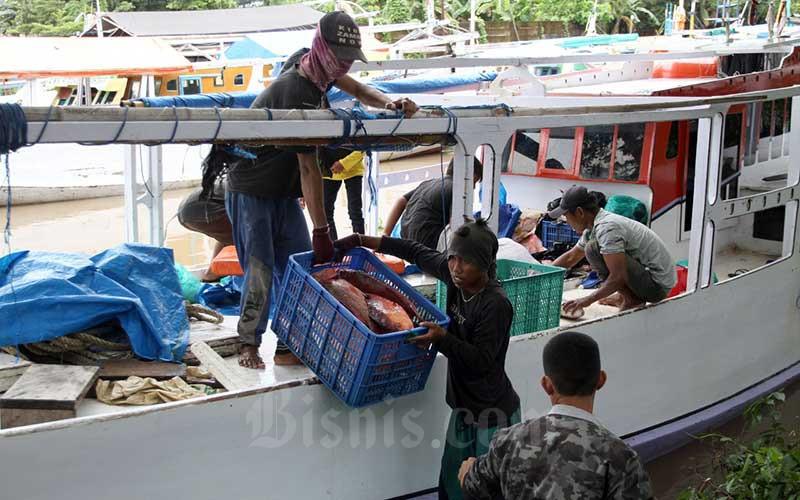 Nelayan memindahkan ikan hasil tangkapan dari kapal di Makassar, Sulawesi Selatan, Senin (22/2/2021). Sepanjang 2020, ekspor komoditas kelautan dan perikanan dari Makassar, Sulawesi Selatan telah menjangkau 50 negara dengan perolehan devisa senilai Rp5,47 triliun. Bisnis/Paulus Tandi Bone