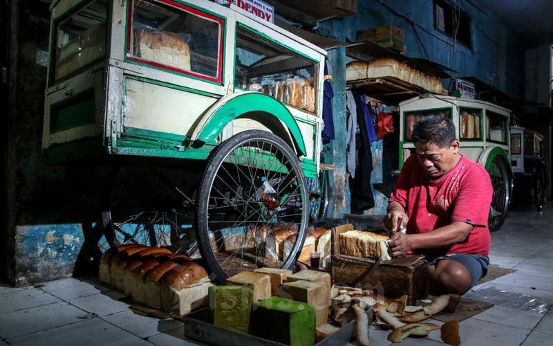 Pekerja melakukan pemotongan roti di Tempat Pembuatan Roti dan Kue Dendy di Menteng Atas, Jakarta, Selasa (23/2/2021). Menteri Keuangan Sri Mulyani Indrawati mencatat alokasi dana Penanganan Ekonomi Nasional (PEN) tahun 2021 untuk mendukung UMKM dan pembiayaan korporasi sebesar Rp187,17 triliun. Bisnis/Eusebio Chrysnamurti