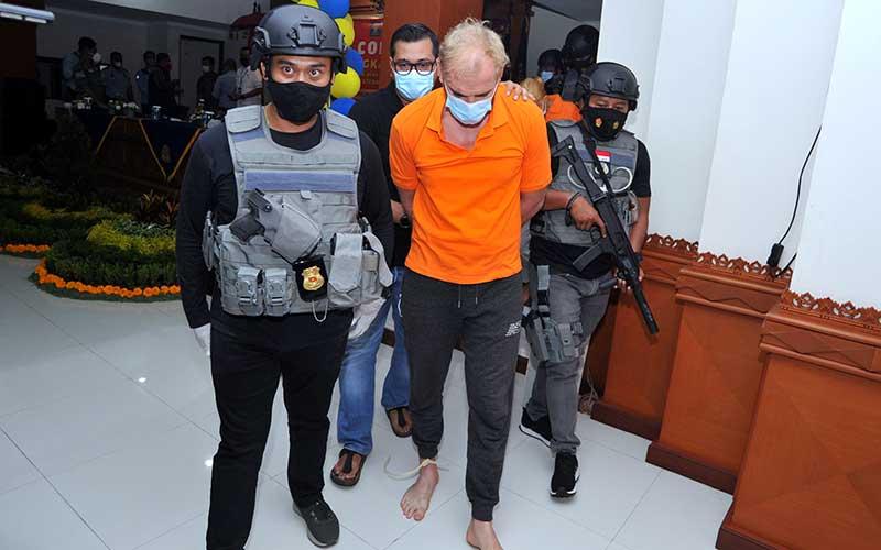 Warga negara Rusia Andrei Kovalenka alias Andrew Ayer (tengah) digiring petugas saat rilis di Kantor Imigrasi Kelas I Khusus TPI Ngurah Rai, Badung, Bali, Rabu (24/2/2021). Andrei Kovalenka yang juga merupakan buronan Interpol tersebut bersama pasangannya Ekaterina Trubkina berhasil ditangkap di kawasan Seminyak, Bali, usai melarikan diri dari Kantor Imigrasi Ngurah Rai sejak Kamis (11/2) lalu saat proses administrasi pemindahannya ke Rumah Detensi Imigrasi Denpasar untuk menunggu pendeportasian setelah sebelumnya menjalani hukuman pidana di Lapas Kerobokan karena kasus narkotika. ANTARA FOTO/Fikri Yusuf