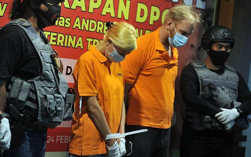 Dua orang warga negara Rusia Andrei Kovalenka alias Andrew Ayer (kanan) dan Ekaterina Trubkina (tengah) dihadirkan petugas saat rilis di Kantor Imigrasi Kelas I Khusus TPI Ngurah Rai, Badung, Bali, Rabu (24/2/2021). Andrei Kovalenka yang juga merupakan buronan Interpol tersebut bersama pasangannya Ekaterina Trubkina berhasil ditangkap di kawasan Seminyak, Bali, usai melarikan diri dari Kantor Imigrasi Ngurah Rai sejak Kamis (11/2) lalu saat proses administrasi pemindahannya ke Rumah Detensi Imigrasi Denpasar untuk menunggu pendeportasian setelah sebelumnya menjalani hukuman pidana di Lapas Kerobokan karena kasus narkotika. ANTARA FOTO/Fikri Yusuf