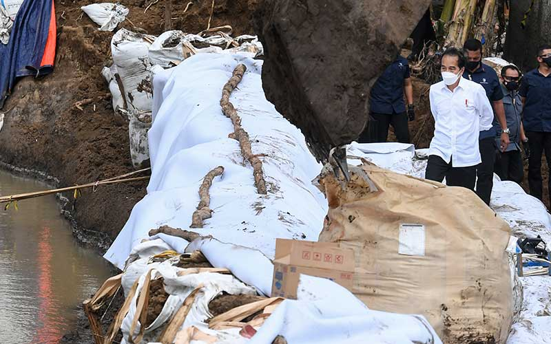 Presiden Joko Widodo berjalan di atas tanggul darurat saat meninjau lokasi jebolnya tanggul Sungai Citarum di Pebayuran, Kabupaten Bekasi, Jawa Barat, Rabu (24/2/2021). Akibat jebolnya tanggul Sungai Citarum tersebut menyebabkan banjir di 134 titik lokasi pada 19 kecamatan di Kabupaten Bekasi dan sebanyak 27.928 kepala keluarga terdampak banjir. ANTARA FOTO/Hafidz Mubarak A