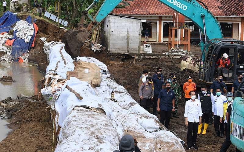 Presiden Joko Widodo (keempat kanan) didampingi Menteri PUPR Basoeki Hadimoeljono (kanan), Gubernur Jawa Barat Ridwan Kamil (ketiga kanan) dan Bupati Bekasi Eka Supria Atmaja (kedua kanan) meninjau lokasi jebolnya tanggul Sungai Citarum di Pebayuran, Kabupaten Bekasi, Jawa Barat, Rabu (24/2/2021). Akibat jebolnya tanggul Sungai Citarum tersebut menyebabkan banjir di 134 titik lokasi pada 19 kecamatan di Kabupaten Bekasi dan sebanyak 27.928 kepala keluarga terdampak banjir. ANTARA FOTO/Hafidz Mubarak A