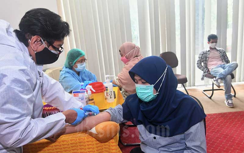 Petugas mengambil darah untuk tes serologi di Jakarta, Kamis (25/2/2021). Bisnis Indonesia bekerja sama dengan Prodia menggelar tes serologi antibodi (Anti SARS-CoV-2-Kualitatif). Tes yang digunakan sebagai skrining awal ini diikuti sekitar 100 orang karyawan Bisnis Indonesia. Tes imuno serologi ini merupakan pemeriksaan yang dilakukan untuk mendeteksi antibodi terhadap SARS-CoV-2 menggunakan protein rekombinan yang merepresentasikan antigen nucleocapsid (N) secara kualitatif pada sampel serum atau plasma yang dikombinasikan dengan pemeriksaan SARS-CoV-2 Ag. Bisnis/Abdurachman