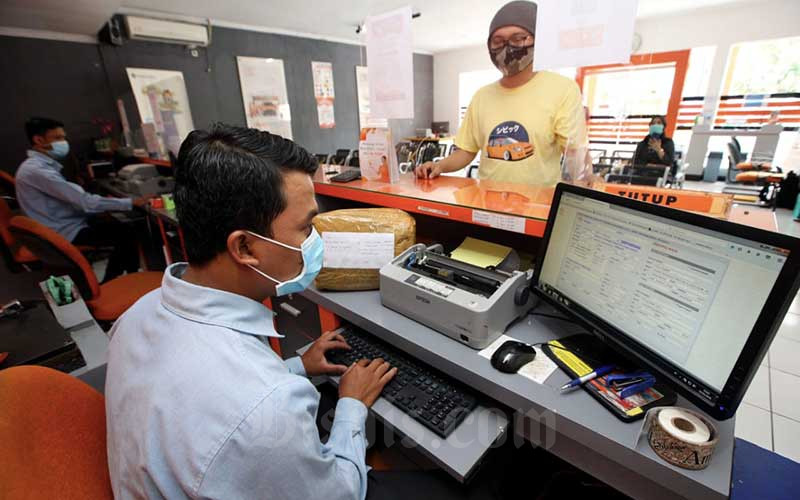 Petugas melayani pelanggan yang akan mengirim paket barang di Kantor Pos Sumedang, Kabupaten Sumedang, Jawa Barat, Kamis (25/2/2021). PT Pos Indonesia (Persero) memastikan tahun ini akan menargetkan pertumbuhan di sisi kurir sebesar 45 persen dan di sisi logistik 92 persen. Hal tersebut merupakan tantangan sekaligus peluang bagi Pos Indonesia untuk melebarkan size bisnisnya. Bisnis/Rachman
