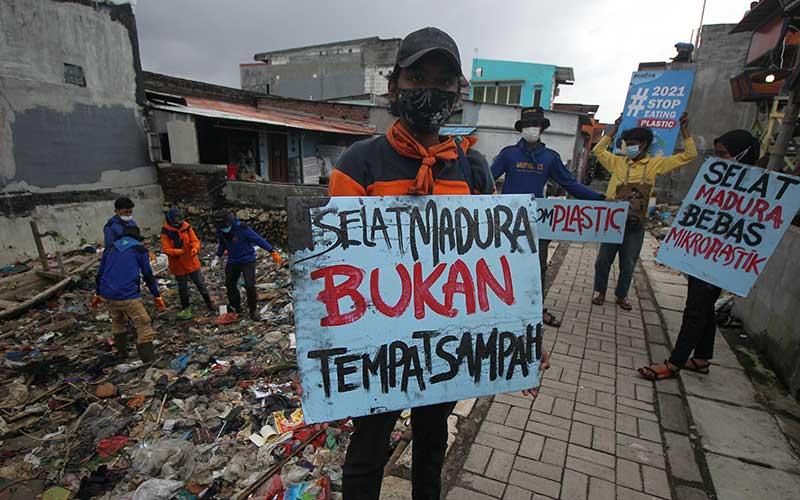Aktivis lingkungan memunguti sampah plastik saat mengkampanyekan #2021stopmakanplastik di pesisir Kenjeran, Surabaya, Jawa Timur, Kamis (25/2/2021). Aksi yang dilakukan oleh Ecoton, Komunitas Tolak Plastik dan sejumlah mahasiswa tersebut dilakukan untuk mengajak masyarakat tidak membuang sampah plastik sembarangan serta mengurangi penggunaan plastik sekali pakai.  ANTARA FOTO/Didik Suhartono