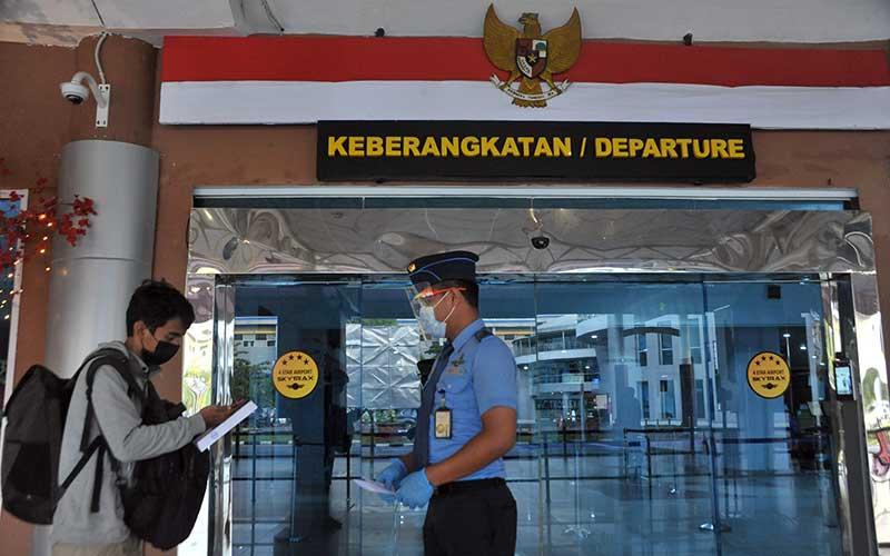 Petugas keamanan memeriksa tiket calon penumpang pesawat udara di Bandara Sultan Mahmud Badaruddin II, Palembang, Sumatera Selatan, Selasa (2/3/2021). Badan Pusat Statistik (BPS) melaporkan jumlah penumpang angkutan udara domestik pada Januari 2021 sebanyak 2,34 juta orang atau mengalami penurunan bila dibandingkan dengan Desember 2020 yang sebanyak 3,18 juta orang disebabkan oleh kewajiban tes Covid-19 dan imbauan pembatasan keberangkatan. ANTARA FOTO/Feny Selly