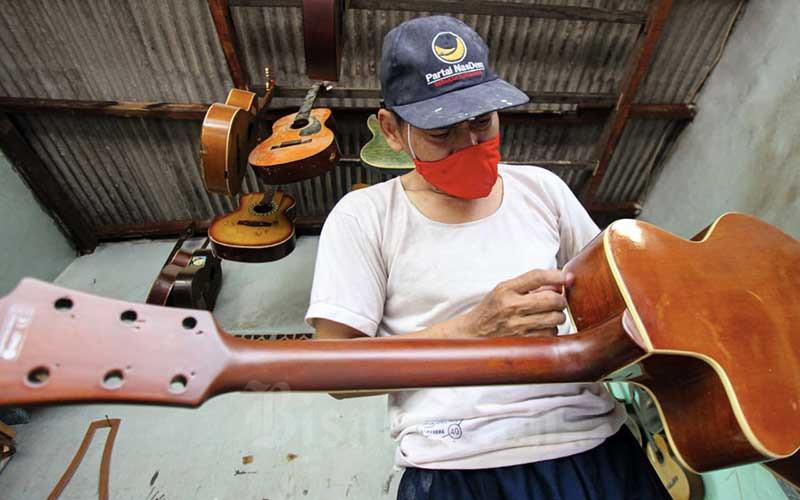 Pekerja beraktivitas di sentra produksi dan reparasi gitar Pak Manto di Jalan Langgar II, Pejaten Timur, Pasar Minggu, Jakarta Selatan, Rabu (3/3/2021). Pemerintah menyatakan bantuan tunai untuk pengusaha mikro, kecil, dan menengah (UMKM) akan disalurkan mulai Maret 2021. Dirjen Anggaran Kementerian Keuangan Askolani mengatakan ada 14 juta UMKM yang akan mendapatkan bantuan tunai senilai Rp1,2 juta, dengan total anggaran sebesar Rp17,34 triliun. Bisnis/Arief Hermawan P