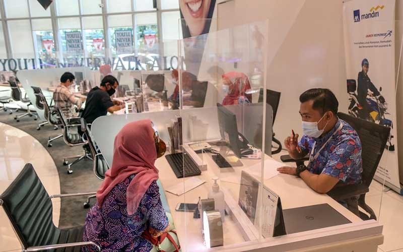 Karyawan melayani nasabah di Kantor Pusat AXA Mandiri, Jakarta, Rabu (3/3/2021). PT AXA Mandiri Financial Services (AXA Mandiri) tahun ini akan lebih mengoptimalkan peluang digitalisasi dalam memasarkan produk asuransi termasuk menyediakan produk yang sesuai dengan kebutuhan dan kemampuan nasabah. AXA Mandiri pada 2020 mencatatkan kinerja klaim asuransi sebesar Rp4,8 triliun, jumlah klaim yang dibayarkan tersebut turun dibandingkan dengan 2019, yang mencapai Rp5,3 triliun. Bisnis/Eusebio Chrysnamurti