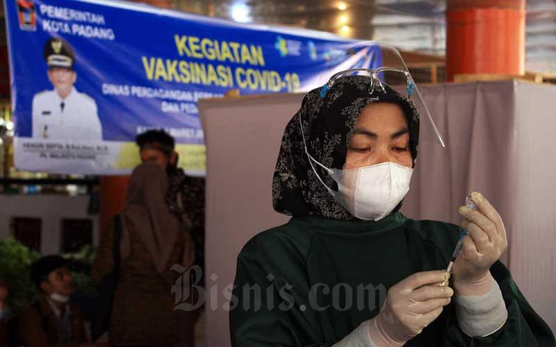 Petugas bersiap menyuntikan vaksin Covid-19 kepada pedagang di Pasar Raya Kota Padang, Sumatera Barat, Kamis (4/3/2021). Vaksinasi ini digelar oleh Dinas Perdagangan Kota Padang terhadap para pedagang yang ada di sejumlah pasar serta turut melibatkan petugas pasar. Pemko Padang berharap vaksinasi itu dapat menciptakan rasa aman dan membuat ekonomi tangguh. Bisnis/Noli Hendra