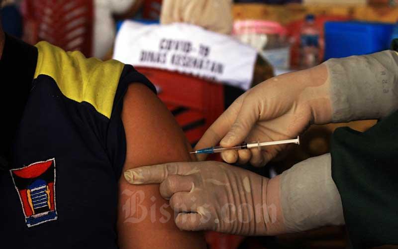 Pedagang disuntik vaksin di Pasar Raya Kota Padang, Sumatera Barat, Kamis (4/3/2021). Vaksinasi ini digelar oleh Dinas Perdagangan Kota Padang terhadap para pedagang yang ada di sejumlah pasar serta turut melibatkan petugas pasar. Pemko Padang berharap vaksinasi itu dapat menciptakan rasa aman dan membuat ekonomi tangguh. Bisnis/Noli Hendra
