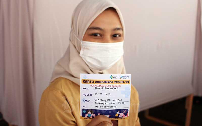 Pedagang menunjukan surat keterangan seusai disuntik vaksin di Pasar Raya Kota Padang, Sumatera Barat, Kamis (4/3/2021). Vaksinasi ini digelar oleh Dinas Perdagangan Kota Padang terhadap para pedagang yang ada di sejumlah pasar serta turut melibatkan petugas pasar. Pemko Padang berharap vaksinasi itu dapat menciptakan rasa aman dan membuat ekonomi tangguh. Bisnis/Noli Hendra