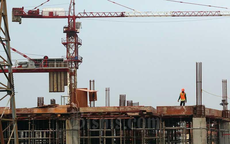 Pekerja menyelesaikan proyek pembangunan gedung bertingkat di Jakarta, Minggu (7/3/2021). Kementerian Perindustrian (Kemenperin) menilai industri besi dan baja akan mengeliat seiring dengan optimisme sektor konstruksi, pemerintah berkomitmen mendukung peningkatan produksi dan penyerapan baja konstruksi dalam proyek nasional. Bisnis/Eusebio Chrysnamurti