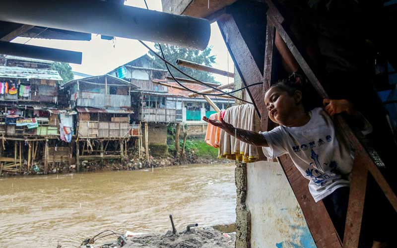 Seorang anak bermain di bantaran Sungai Ciliwung, Jakarta, Minggu (7/3/2021). Wakil Gubernur DKI Jakarta Ahmad Riza Patria mengatakan pembebasan lahan untuk normalisasi sungai Ciliwung membutuhkan anggaran sebesar Rp 5 triliun. Saat ini bantaran sungai Ciliwung yang sudah dibebaskan dan bisa dilakukan normalisasi sepanjang 7,6 kilometer, sisanya sepanjang 17 kilometer belum dinormalisasi. Bisnis/Eusebio Chrysnamurti