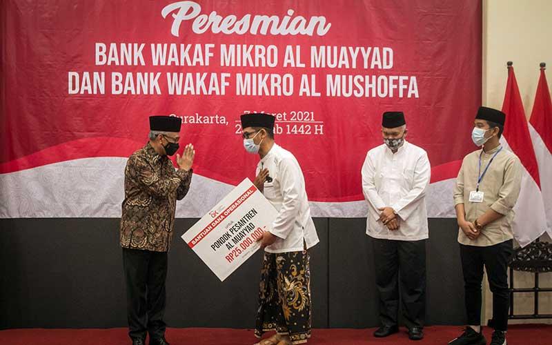Ketua Dewan Komisioner Otoritas Jasa Keuangan (OJK) Wimboh Santoso (kiri) didampingi Wali Kota Solo Gibran Rakabuming Raka (kanan) dan Kepala OJK Solo Eko Yunianto (kedua kanan) menyerahkan bantuan kepada perwakilan Pondok Pesantren Al Muayyad pada acara Peresmian Bank Wakaf Mikro (BWM) Al Muayyad dan Al Mushoffa di Kantor OJK, Solo, Jawa Tengah, Minggu (7/3/2021). OJK saat ini telah mendirikan 60 BWM dengan diresmikannya BWM di Pondok Pesantren Al Muayyad dan Ponpes Al Qur'aniyy Azzayadiy, dengan total penerima manfaat sekitar 41.436 nasabah dan total pembiayaan mencapai Rp60,6 miliar. ANTARA FOTO/Mohammad Ayudha
