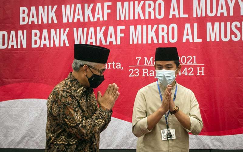 Ketua Dewan Komisioner Otoritas Jasa Keuangan (OJK) Wimboh Santoso (kiri) menyapa Wali Kota Solo Gibran Rakabuming Raka (kanan) pada acara Peresmian Bank Wakaf Mikro (BWM) Al Muayyad dan Al Mushoffa di Kantor OJK, Solo, Jawa Tengah, Minggu (7/3/2021). OJK saat ini telah mendirikan 60 BWM dengan diresmikannya BWM di Pondok Pesantren Al Muayyad dan Ponpes Al Qur'aniyy Azzayadiy, dengan total penerima manfaat sekitar 41.436 nasabah dan total pembiayaan mencapai Rp60,6 miliar. ANTARA FOTO/Mohammad Ayudha