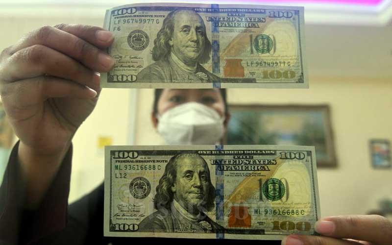 Karyawati menunjukan dolar AS di Jakarta, Selasa (9/3/2021). Nilai tukar rupiah terhadap dolar Amerika Serikat (AS)  melanjutkan pelemahannya. Hingga akhir perdagangan nilai tukar rupiah di pasar spot ditutup melemah 45 poin atau 0,31 persen ke level Rp14.405 per dolar AS. Penurunan nilai tukar rupiah terjadi di tengah tren penguatan dolar AS terhadap mata uang dunia di tengah tren peningkatan yield Treasury AS. Bisnis/Abdurachman