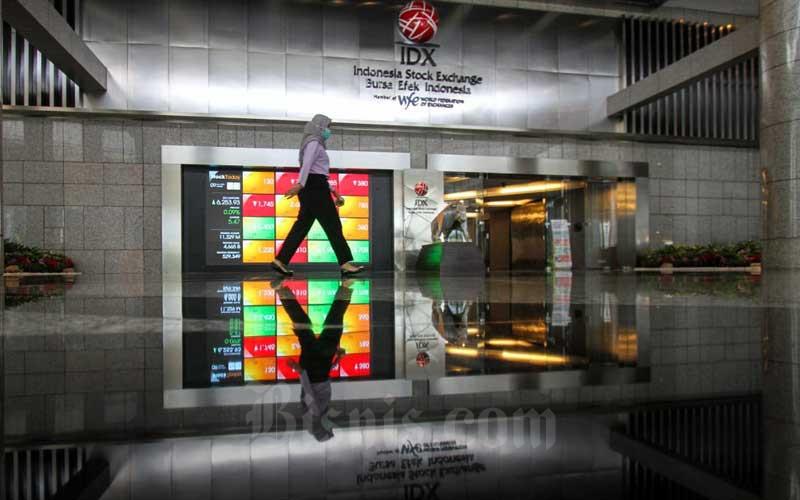 Karyawan melintas di depan layar pergerakan saham di kantor PT Bursa Efek Indonesia, Jakarta, Selasa (9/3/2021). Berdasarkan data Bloomberg, Indeks Harga Saham Gabungan (IHSG) ditutup melemah 0,78 persen atau 48,82 poin ke level 6.199,65 pada akhir perdagangan Selasa (9/3). Bisnis/Arief Hermawan P