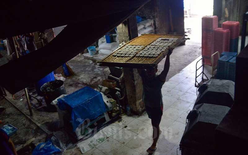 Pekerja membawa kerupuk mentah di UMKM Kerupuk Melati, Jakarta, Selasa (6/4/2021). Pemerintah berencana menaikkan plafon Kredit Usaha Rakyat (KUR) untuk usaha mikro, kecil, dan menengah (UMKM) menjadi Rp 20 miliar dari sebelumnya Rp 500 juta. Menteri Koperasi dan UKM Teten Masduki menyebutkan, hal tersebut sesuai arahan Presiden Joko Widodo dalam Rapat Terbatas tentang Peningkatan Porsi Kredit Perbankan untuk Usaha Mikro dan Kecil.Bisnis/Fanny Kusumawardhani