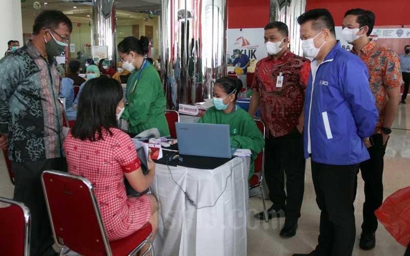 Kepala Otoritas Jasa Keuangan Regional 6 Sulampua Moh Nurdin Subandi yang juga Ketua Forum Komunikasi Industri Jasa Keuangan (FKIJK) Sulawesi Selatan dan Barat (kiri) didampingi Wakil Ketua II FKIJK yang juga Regional Manager Kawasan Timur Indonesia Bank Panin Andi Hudli Huduri (ketiga kanan), dan Kepala Kantor Cabang Utama Bank BCA Makassar yang juga Bendahara FKIJK Tony Djajasaputra (kedua kanan) meninjau prosesi vaksin para pelaku industry jasa keuangan di Makassar, Sulawesi Selatan, Selasa (6/4/2021). Dihari pertama FKIJK menargetkan 500 orang untuk di vaksin dari total sebanyak 1500 orang. Bisnis/Paulus Tandi Bone
