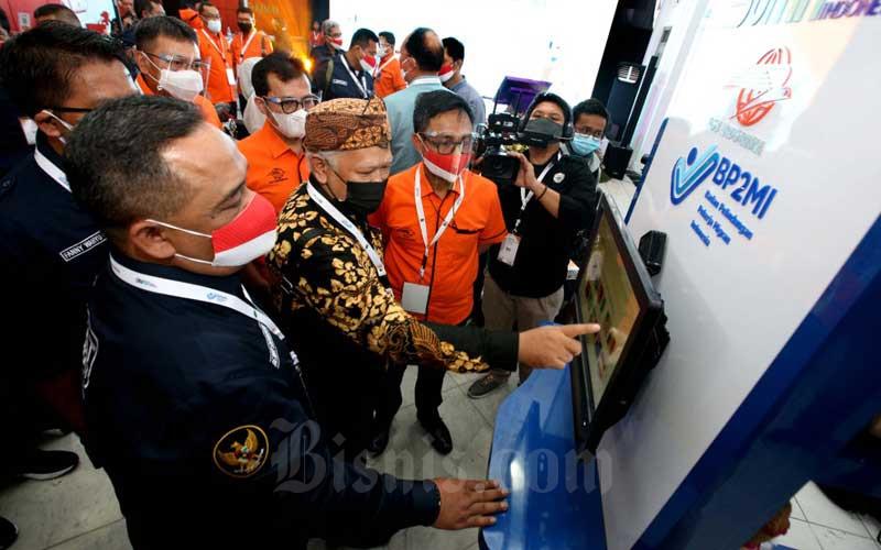 Kepala Badan Perlindungan Pekerja Migran Indonesia (BP2MI) Benny Rhamdani (kiri) dan Direktur Utama PT Pos Indonesia (Persero) Faizal Rochmad Djoemadi (ketiga kiri) meninjau salah satu fasilitas di pojok Pos Migran Indonesia usai peluncurannya di Kantor Pos Besar Bandung, Jawa Barat, Selasa (6/4/2021). Pos Indonesia bersama BP2MI meluncurkan Pos Migran Indonesia untuk memfasilitasi kebutuhan Pekerja Migran Indonesia terhadap layanan Pos Indonesia baik dalam layanan keuangan maupun layanan akses informasi melalui jaringan Pos yang ada di seluruh Indonesia. Bisnis/Rachman