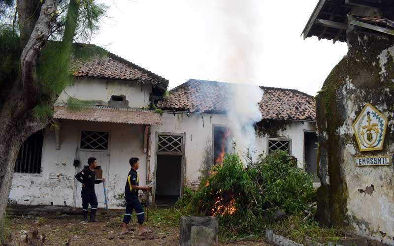 Pekerja membersihkan lingkungan bekas Rumah Tahanan Militer (RTM) di Kota Madiun, Jawa Timur, Selasa (6/4/2021). Pemkot Madiun mempersiapkan bangunan bekas RTM tersebut untuk menampung para pemudik Lebaran yang positif Covid-19 guna menjalani isolasi. ANTARA FOTO/Siswowidodo