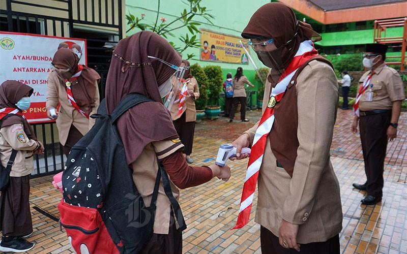 Guru SDN Kenari 08 memeriksa suhu tubuh siswa sebelum memasuki ruang kelas, Jakarta, Rabu (7/4/2021). Pemerintah Provinsi DKI Jakarta mulai melakukan uji coba pembelajaran tatap muka mulai Rabu hingga 29 April 2021 dengan protokol kesehatan Covid-19 yang ketat. Skema yang diterapkan adalah pembelajaran tatap muka secara bergantian dengan membatasi jumlah siswa di setiap kelas maksimal 50 persen dari kapasitas. Bisnis/Suselo Jati