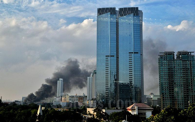 Kepulan asap hitam yang berasal dari lokasi kebakaran di Pasar Lontar atau Pasar Kambing di Jalan Sabeni, Tanah Abang, Jakarta, Kamis (8/4/2021). Sebanyak 17 unit mobil pemadam dikerahkan untuk memadamkan kebakaran di lokasi tersebut. Bisnis/Abdurachman.