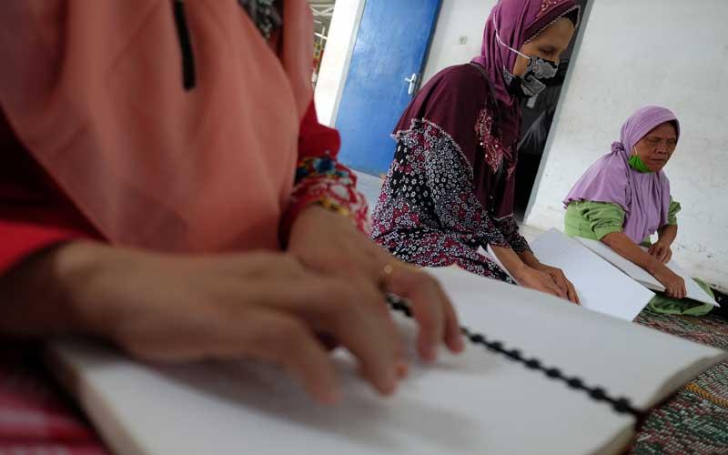 Penyandang tunanetra membaca Al Quran yang dicetak dengan huruf braille di Medan, Sumatra Utara, Kamis (15/4/2021). Kegiatan rutin yang dilaksanakan Dewan Perwakilan Daerah Persatuan Tuna Netra Indonesia (Pertuni) Sumut tersebut untuk guna melatih kemampuan membaca Al Quran sekaligus meningkatkan ibadah pada bulan Ramadhan. ANTARA FOTO/Irsan Mulyadi