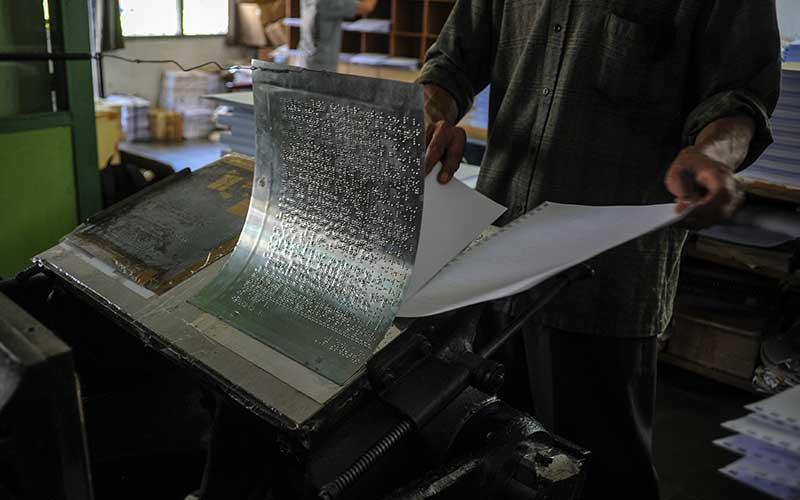 Pekerja mencetak kertas menggunakan mesin cetak huruf braile merk Thomson tahun 1952 untuk saat produksi Al Quran Braile di Percetakan Yayasan Penyantun Wyata Guna, Bandung, Jawa Barat, Sabtu (17/4/2021). Pada Bulan Ramadan tahun ini, percetakan tersebut memproduksi 150 set Al Quran Braile yang kemudian akan di distribusikan ke berbagai majelis taklim serta lembaga keagamaan di seluruh Indonesia. ANTARA FOTO/Raisan Al Farisi
