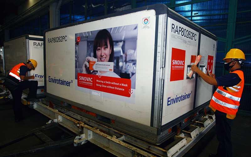 Pekerja membawa Envirotainer berisi vaksin Covid-19 Sinovac setibanya dari Beijing di Terminal Cargo Bandara Soekarno Hatta, Tangerang, Banten, Minggu (18/4/2021). Sebanyak enam juta dosis vaksin Covid-19 Sinovac yang dibawa dengan pesawat Garuda Indonesia tersebut, selanjutnya dibawa ke Bio Farma Bandung sebelum didistribusikan ke Kota dan Kabupaten di Indonesia. ANTARA/Muhammad Iqbal