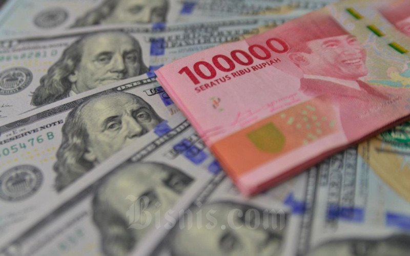 Petugas menunjukkan mata uang dolar AS dan rupiah di Money Changer, Jakarta, Senin (19/4/2021). Bisnis/Fanny Kusumawardhani