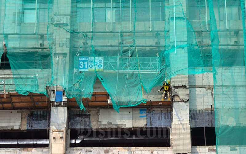 Pekerja melakukan renovasi Gedung Sarinah di Jakarta, Senin (19/4/2021). Kementerian Ketenagakerjaan mengeluarkan Surat Edaran nomor M/6/HK.04/IV/2021 tentang Pelaksanaan Pemberian Tunjangan Hari Raya (THR) Keagamaan Tahun 2021 bagi pekerja/buruh di perusahaan pada 12 April 2021 yang isinya antara lain tentang denda dan sanksi yang dikenakan bagi perusahaan jika tidak melakukan kewajiban membayar THR kepada karyawannya termasuk perusahaan yang terdampak Covid-19 sehingga tidak mampu memberikan THR 2021 sesuai dengan waktu yang telah ditentukan. Bisnis/Fanny Kusumawardhani
