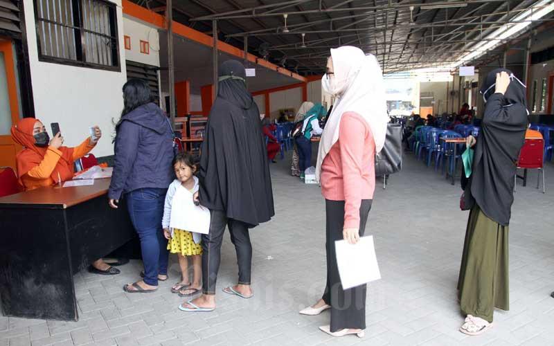 Petugas memotret penerima manfaat saat akan melakukan pembayaran Bantuan Sosial Tunai (BST) kepada Keluarga Penerima Manfaat (KPM) di Makassar, Sulawesi Selatan, Selasa (20/4/2021). Pemerintah menganggarkan Rp12 triliun dengan rincian Rp300 ribu per KPM dengan menyasar 10 juta keluarga. Bisnis/Paulus Tandi Bone