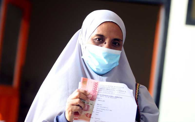 Warga memperlihatkan uang yang diterimanya dari program Bantuan Sosial Tunai (BST) di Makassar, Sulawesi Selatan, Selasa (20/4/2021). Pemerintah menganggarkan Rp12 triliun dengan rincian Rp300 ribu per KPM dengan menyasar 10 juta keluarga. Bisnis/Paulus Tandi Bone
