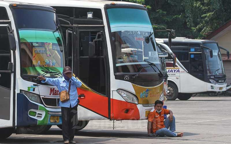 Awak bus Antar Kota Antar Provinsi (AKAP) menunggu penumpang di Terminal Kampung Rambutan, Jakarta, Rabu (21/4/2021). Ketua Bidang Advokasi dan Kemasyarakatan Masyarakat Transportasi Indonesia (MTI) Pusat Djoko Setijowarno menyampaikan bahwa pemerintah perlu memberikan skema bantuan kepada perusahaan sektor transportasi AKAP, agar dapat memberikan THR kepada pegawai mereka. Hal itu mengingat kebijakan larangan mudik yang dikeluarkan pemerintah akan mempengaruhi penghasilan pengemudi, karena sebagian pengemudi bus AKAP tidak mendapat gaji bulanan melainkan hanya mendapatkan upah ketika mengemudikan bus. Bisnis/Arief Hermawan P