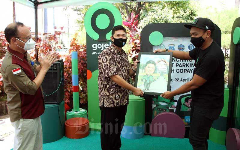 VP Gojek Indonesia Timur Annandita Danaatmaja (kanan) menyerahkan cinderamata kepada Dirut Perusahaan Daerah Parkir Irham Syah Gaffar (tengah) disaksikan Deputi Direktur Bank Indonesia Sulawesi Selatan Ali Akhfan (kiri) disela sela acara peluncuran pembayaran parkir smart bersama Go Pay di Makassar, Sulawesi Selatan, Kamis (22/4/2021). Untuk tahap awal sistim pembayaran parkir yang langsung memotong saldo Gopay tersebut akan ada di 31 titik perparkiran dengan jumlah juru parkir sebanyak 50 orang. Bisnis/Paulus Tandi Bone