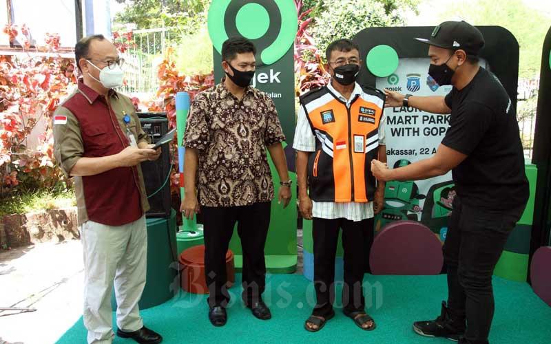 VP Gojek Indonesia Timur Annandita Danaatmaja (kanan) menyematkan jaket secara simbolis kepada juru parkir disaksikan Dirut Perusahaan Daerah Parkir Irham Syah Gaffar (kedua kiri) dan Deputi Direktur Bank Indonesia Sulawesi Selatan Ali Akhfan (kiri) pada acara peresmian smart parkir bersama Gopay di Makassar Sulawesi Selatan, Kamis (22/4/2021). Untuk tahap awal sistim pembayaran parkir yang langsung memotong saldo Go Pay tersebut aka nada di 31 titik perparkiran dengan jumlah juru parkir sebanyak 50 orang. Bisnis/Paulus Tandi Bone