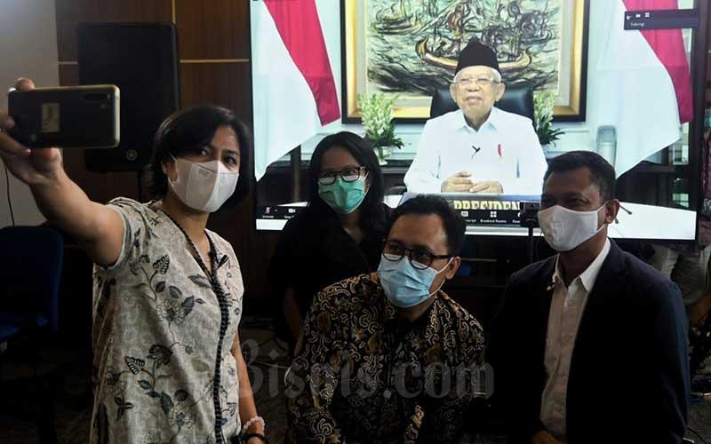 Wakil Presiden Republik Indonesia Ma`ruf Amin (dilayar) berfoto bersama dengan Pemimpin Redaksi Bisnis Indonesia Maria Y Benyamin (dari kiri), Wakil Pemimpin Redaksi  Rahayuningsih, Redaktur Pelaksana Galih Kurniawan, dan Wakil Pemimpin Redaksi Fahmi Achmad seusai wawancara secara virtual di Jakarta, Jumat (23/4/2021). Menurut Wapres diperlukan  komitmen kuat untuk mengembangkan ekonomi dan keuangan syariah yang diikuti upaya nyata berbagai pihak. Berdasarkan Peraturan Presiden (Perpres) Nomor 28 Tahun 2020 tentang Komite Nasional Ekonomi dan Keuangan Syariah (KNEKS), pengembangan ekonomi dan keuangan syariah difokuskan pada 4 (empat) hal yaitu pengembangan industri produk halal, pengembangan industri keuangan syariah, pengembangan dana sosial syariah, dan pengembangan serta perluasan kegiatan usaha syariah. Bisnis/Abdurachman