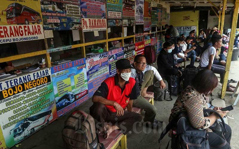 Calon penumpang menunggu di loket penjualan tiket bus AKAP di terminal bayangan Pondok Pinang, Jakarta, Jumat (23/4/2021). Kementerian Perhubungan (Kemenhub) hingga kini belum menerbitkan aturan tentang pengendalian transportasi selama Idulfitri 1442 H Dalam Rangka Pencegahan Penyebaran Covid-19 sehingga menjadi ganjalan dalam pelarangan mudik. Direktur Eksekutif Institut Studi Transportasi (Instran) Deddy Herlambang mengatakan kendati Satuan Tugas (Satgas) Penanganan Covid-19 telah menerbitkan adendum Surat Edaran (SE) No. 13/2021 tentang Peniadaan Mudik Hari Raya Idul Fitri Tahun 1442 H dan Upaya Pengendalian Penyebaran Covid-19 Selama Bulan Suci Ramadhan 1442 Hijriah tetapi belum dilandasi oleh PM dari Kementerian Perhubungan. Bisnis/Eusebio Chrysnamurti