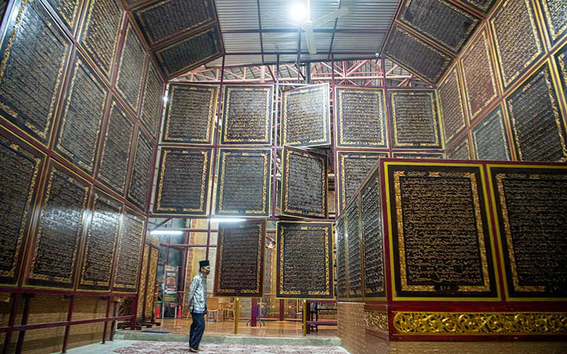 Pengunjung membaca ayat-ayat yang ada di Al Quran Al-Akbar di Palembang, Sumatera Selatan, Jumat (23/4/2021). Keberadaan Al Quran raksasa yang diukir di atas kayu trembesi itu menjadi destinasi wisata religi di Kota Palembang selama bulan Ramadan. ANTARA FOTO/Nova Wahyudi
