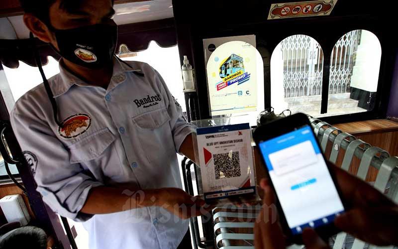 Konsumen melakukan transaksi dengan memindai Quick Response Code Indonesian Standard (QRIS) menggunakan aplikasi layanan keuangan digital BJB DigiCash saat menaiki bus wisata Bandung tour on bus (Bandros) di Bandung, Jawa Barat, Senin (3/5/2021). Berdasarkan data Bank Indonesia, volume transaksi digital banking pada Maret 2021 mencapai 553,6 juta atau meningkat 42,47 persen dibandingkan dengan periode yang sama pada 2020. Adapun nilai transaksi naik 26,44 persen dengan nilai mencapai Rp3.025,6 triliun. Bisnis/Rachman