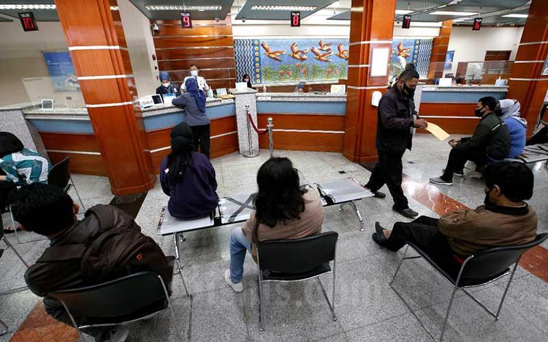 Teller melayani warga yang menukarkan uang di PT Bank Pembangunan Daerah Jawa Barat dan Banten, Tbk. (Bank BJB) Kantor Cabang Utama Bandung, Jawa Barat, Senin (3/5/2021). Selama Ramadan dan menjelang Hari Raya Idulfitri 1442 Hijriah, Bank BJB memproyeksikan kebutuhan uang tunai sebesar Rp15,1 triliun. Dana tersebut akan dialokasikan untuk pemenuhan kebutuhan operasional dan ketersediaan dana ATM di seluruh jaringan kantor Bank BJB di 14 Provinsi di Indonesia. Bisnis/Rachman