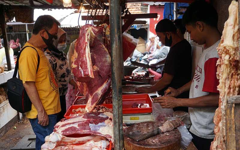 Pedagang daging sapi segar melayani konsumen, di Pasar Kramat Jati, Jakarta, Senin (3/5/2021). BUMN klaster pangan yakni PT Rajawali Nusantara Indonesia (Persero) dan PT Berdikari (Persero) mendatangkan daging sapi beku boneless asal Brasil sebanyak 420 ton secara bertahap untuk menjaga stabilitas harga serta memenuhi ketersediaan pasokan menjelang Idulfitri. Direktur Utama RNI Arief Prasetyo Adi mengatakan upaya menjaga ketersediaan daging sapi ini sejalan dengan peningkatan ketahanan pangan nasional. Bisnis/Suselo Jati