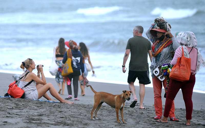 Pedagang pantai menawarkan dagangannya kepada wisatawan mancanegara (wisman) di kawasan Pantai Batu Bolong, Canggu, Badung, Bali, Senin (3/5/2021). Berdasarkan data Badan Pusat Statistik (BPS), secara kumulatif jumlah kunjungan wisman ke Indonesia pada periode bulan Januari-Maret 2021 tercatat sebesar 385.590 kunjungan atau turun sebesar 85,45 persen jika dibandingkan dengan jumlah kunjungan wisman pada periode yang sama pada tahun 2020 dengan jumlah 2,65 juta kunjungan. ANTARA FOTO/Fikri Yusuf